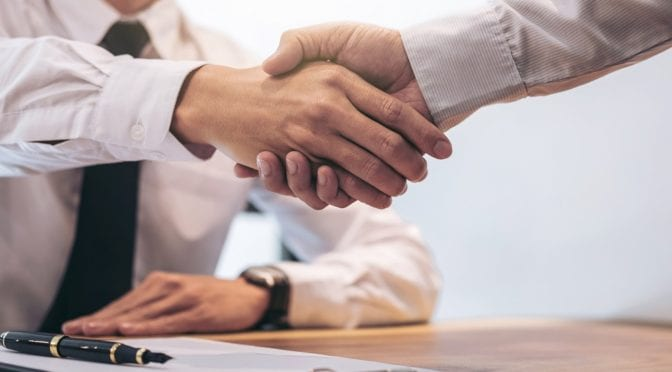 Real estate broker agent and customer shaking hands after signing