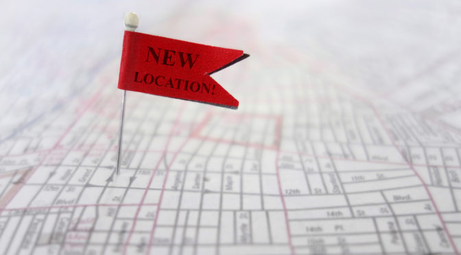 Closeup of a New Location pin flag on a map