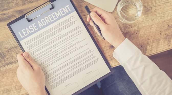 Signing a commercial lease agreement on clipboard